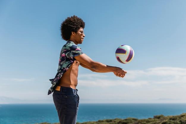 Szczęśliwy człowiek african american rzucanie piłki przeciw błękitne niebo