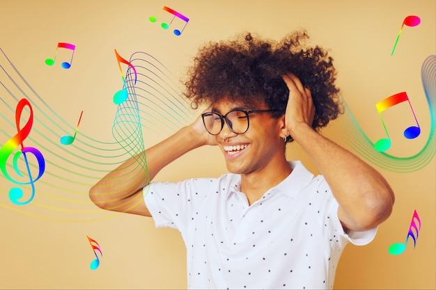 Szczęśliwy człowiek afro tańczy i słucha muzyki
