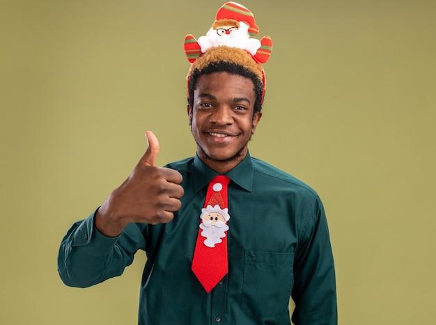 Szczęśliwy człowiek afroamerykanin z śmieszne santa rim i czerwonym krawatem patrząc na kamery pokazując kciuki do góry uśmiechnięty stojący na zielonym tle