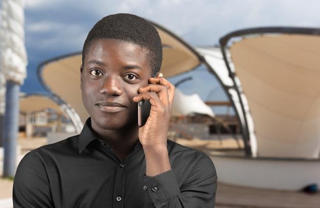 Szczęśliwy człowiek afroamerykański za pomocą telefonu komórkowego