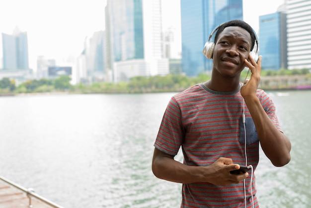 Szczęśliwy człowiek afryki w parku przy użyciu telefonu komórkowego i słuchania muzyki w słuchawkach