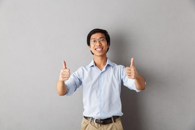Szczęśliwy człowiek azjatycki stojący na białym tle, pokazując kciuki do góry