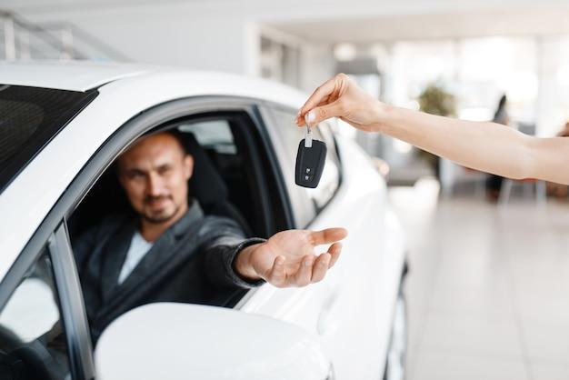 Szczęśliwy człowiek bierze klucz do nowego samochodu w salonie.