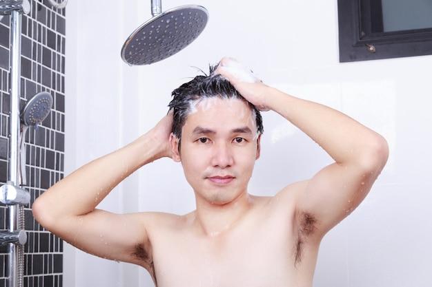 Szczęśliwy człowiek bierze prysznic ze strumieniem deszczowym i myje włosy