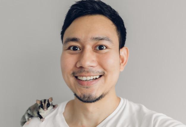 Szczęśliwy człowiek bierze selfie siebie i swojego zwierzaka sugar glider.
