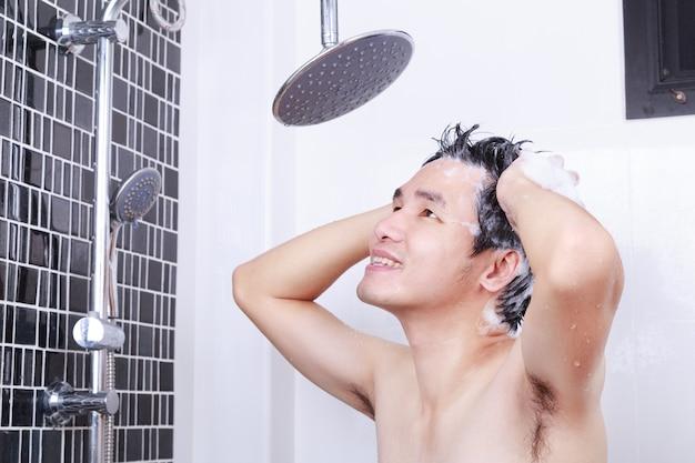Szczęśliwy człowiek biorąc prysznic ze strumieniem deszczowym i mycie włosów w łazience