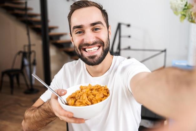 Szczęśliwy człowiek, biorąc selfie, siedząc w kuchni w domu, trzymając miskę z płatkami zbożowymi
