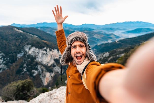 Szczęśliwy człowiek biorąc selfie, wspinaczka górska