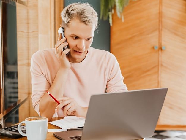 Szczęśliwy człowiek biznesu siedzący w stołówce z laptopem i smartfonem