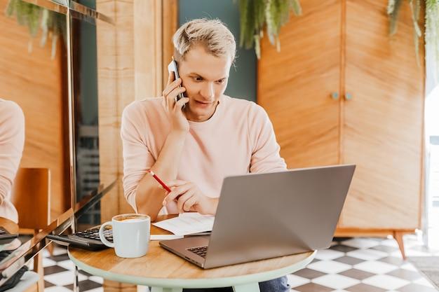 Szczęśliwy człowiek biznesu siedzi w stołówce z laptopa i smartfona. biznesmen wysyła sms-y na smartfonie siedząc w kawiarni, pracując i sprawdzając pocztę e-mail na komputerze