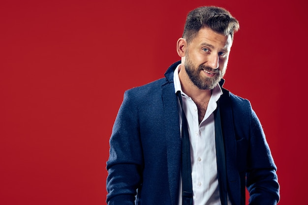 Szczęśliwy człowiek biznesu stojąc i uśmiechając się na białym tle na czerwono. piękny portret męski w połowie długości. młody człowiek emocjonalny. ludzkie emocje, koncepcja wyrazu twarzy
