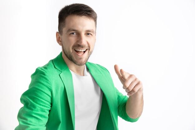 Szczęśliwy człowiek biznesu stojąc, uśmiechając się i wskazując na aparat na białym tle na szarym studio.