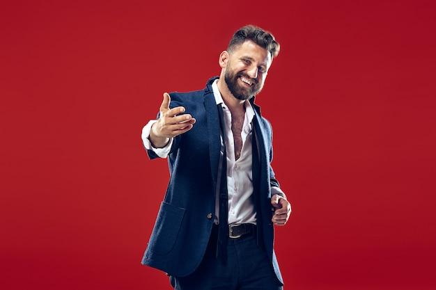 Szczęśliwy człowiek biznesu stojący i uśmiechający się na tle czerwonej ściany