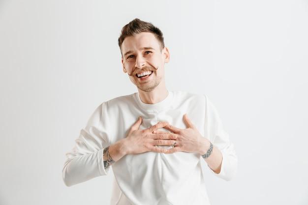 Szczęśliwy człowiek biznesu stojący, uśmiechnięty na białym tle na szarej przestrzeni. piękny portret męski w połowie długości. młody człowiek zadowoli