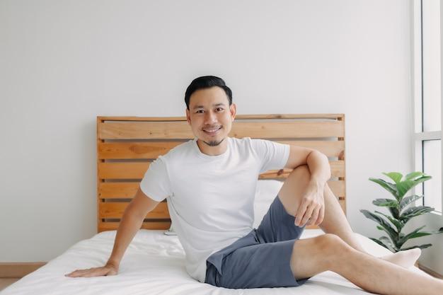 Szczęśliwy człowiek chłodzi i zrelaksowany na swojej koncepcji łóżka zdrowego umysłu