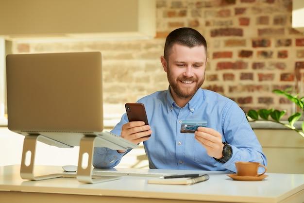 Szczęśliwy człowiek czytający informacje z tyłu karty kredytowej i wpisujący ją na smartfonie, aby dokonać zakupu online w domu