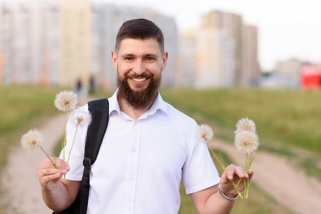 Szczęśliwy człowiek, dając dwa bukiety mleczy i uśmiechając się