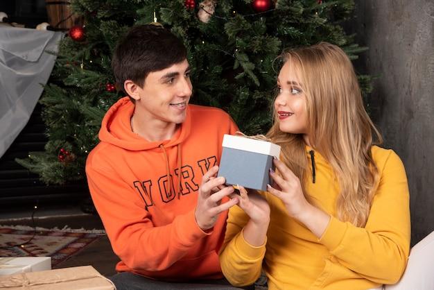 Szczęśliwy człowiek daje boże narodzenie pudełko do swojej dziewczyny w pobliżu choinki.