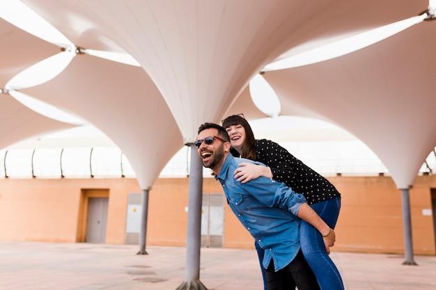 Szczęśliwy człowiek daje jazda piggyback do swojej dziewczyny