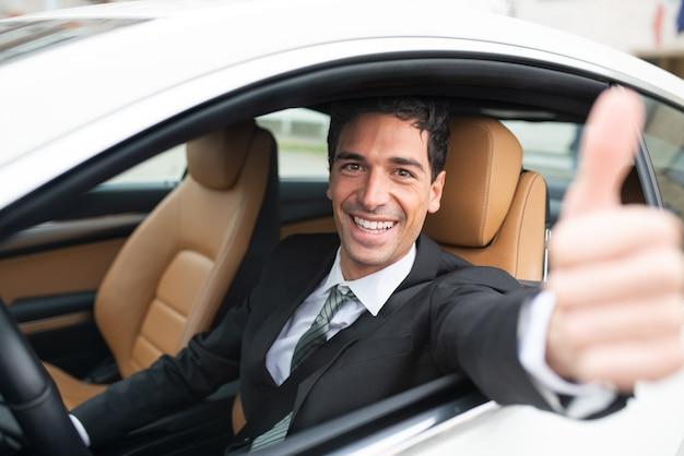 Szczęśliwy człowiek daje kciuki podczas jazdy swoim nowym samochodem