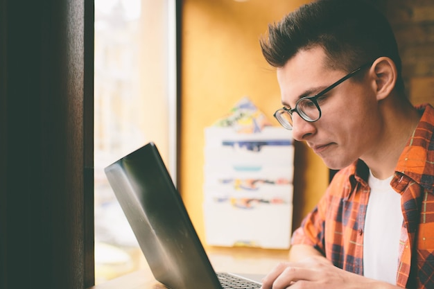 Szczęśliwy człowiek dorywczo za pomocą laptopa w kawiarni