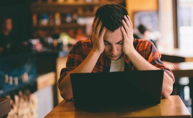Szczęśliwy człowiek dorywczo za pomocą smartfona i laptopa w kawiarni w stresie i przygotowuje się do egzaminów