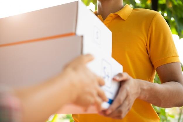 Szczęśliwy człowiek dostawy w mundurze żółta koszulka polo z paczki w ręce