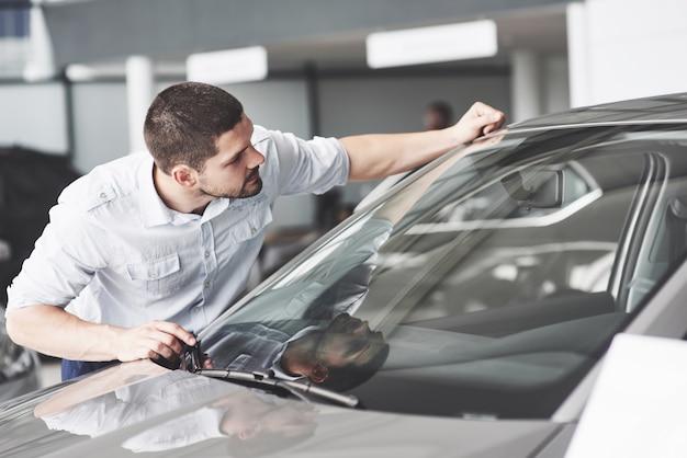Szczęśliwy człowiek dotyka samochodu w salonie samochodowym lub w salonie.