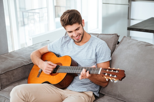 Szczęśliwy człowiek gra na gitarze siedząc na kanapie w domu. patrząc na gitarę.