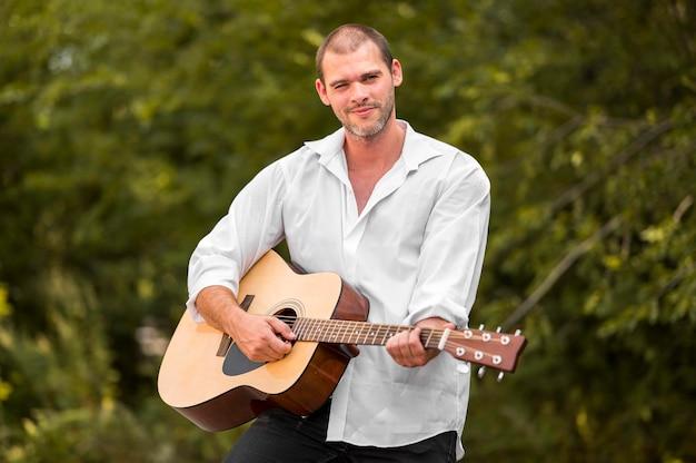 Szczęśliwy człowiek gra na gitarze w naturze