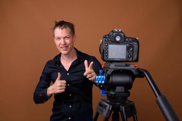 Szczęśliwy człowiek influencer vlogging z aparatem dslr
