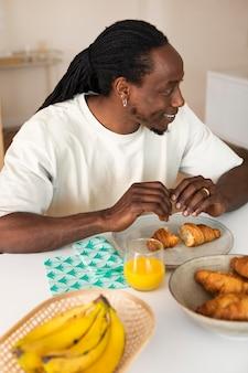 Szczęśliwy człowiek je śniadanie z bananami