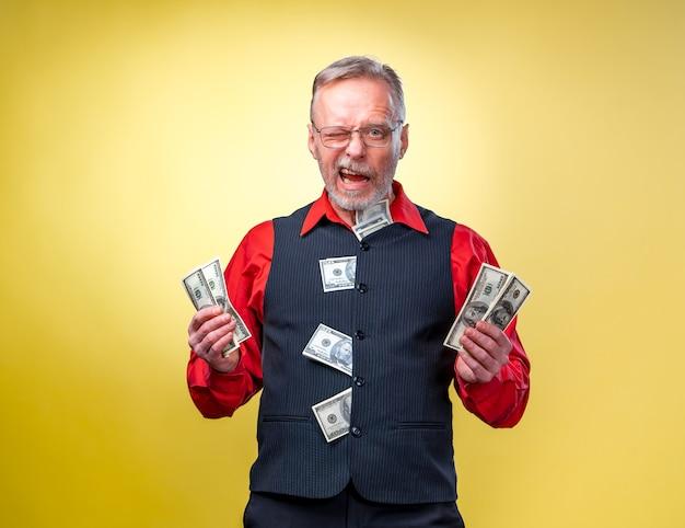 Szczęśliwy człowiek korzystający z pieniędzy. ręce z pieniędzmi, dolarami amerykańskimi, biznesmenem, bogatym w sukcesy. pozytywne emocje wyraz twarzy. mrugając do kamery