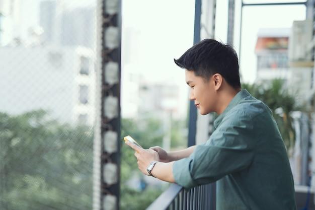Szczęśliwy człowiek korzystający z telefonu komórkowego na balkonie