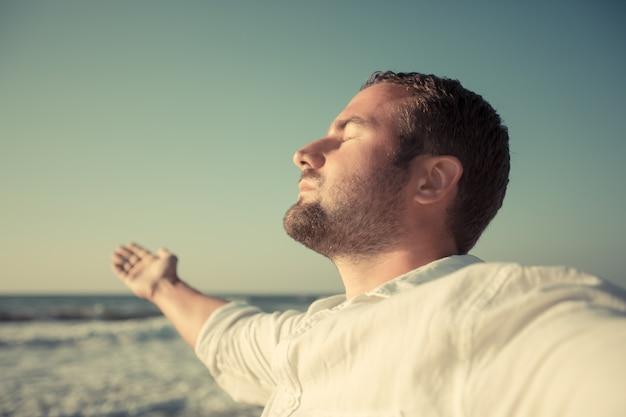 Szczęśliwy człowiek korzystający z życia na plaży koncepcja letnich wakacji i wolności