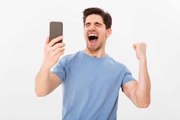 Szczęśliwy człowiek krzyczący w koszulce trzymając smartfon i raduje się z zamkniętymi oczami na szarej ścianie