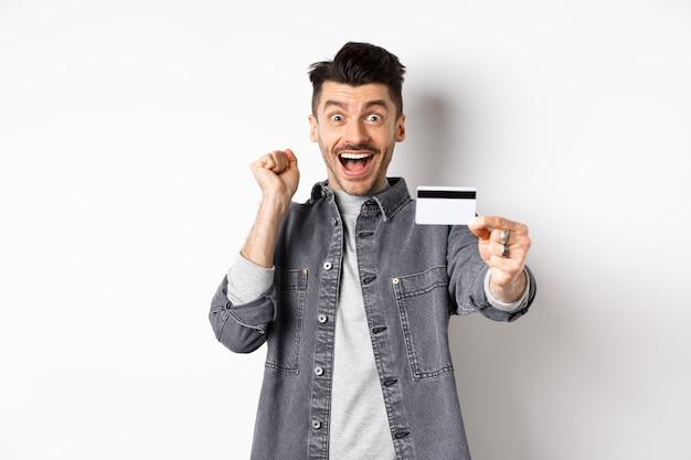Szczęśliwy człowiek krzyczy z podniecenia i pokazuje plastikową kartę kredytową, rekomendując bank, stojąc na białym tle.