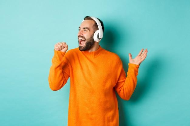 Szczęśliwy człowiek lipsync słuchając muzyki w słuchawkach, trzymając niewidzialny mikrofon, stojąc na turkusowym tle.