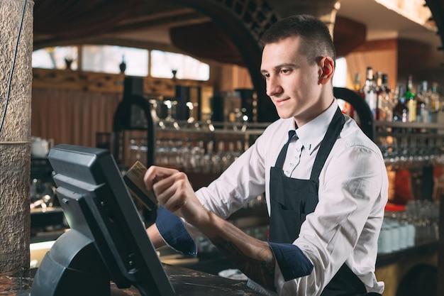 Szczęśliwy człowiek lub kelner w fartuchu przy kasie z kasą pracującą w barze lub kawiarni