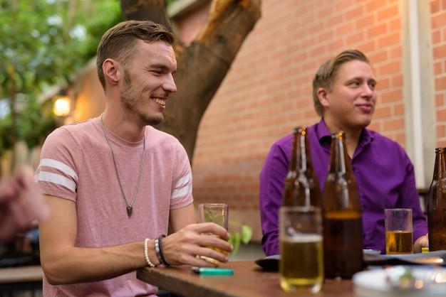 Szczęśliwy człowiek mówi i pije piwo z przyjaciółmi