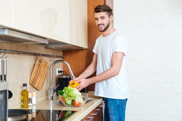 Szczęśliwy człowiek myjący warzywa w kuchni
