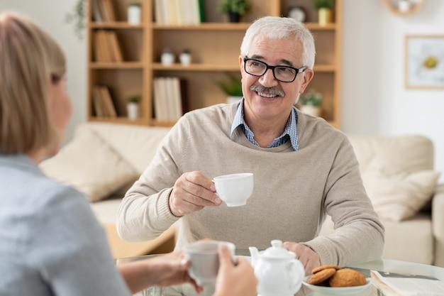 Szczęśliwy człowiek na emeryturze z filiżanką herbaty, patrząc na swoją córkę podczas rozmowy przy stole w środowisku domowym