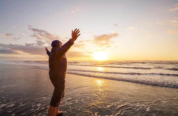 Szczęśliwy człowiek na plaży nad oceanem o zachodzie słońca