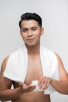 Szczęśliwy człowiek nakłada balsam po goleniu na twarz na białym tle
