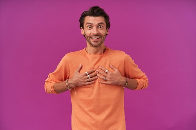 Szczęśliwy człowiek o ciemnych włosach i szczecinie. ubrana w pomarańczowy sweter z podwiniętymi rękawami. posiada bransoletki, pierścionki. wskazując na siebie z podekscytowaniem