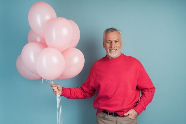 Szczęśliwy człowiek obchodzi trzymając różowe balony.