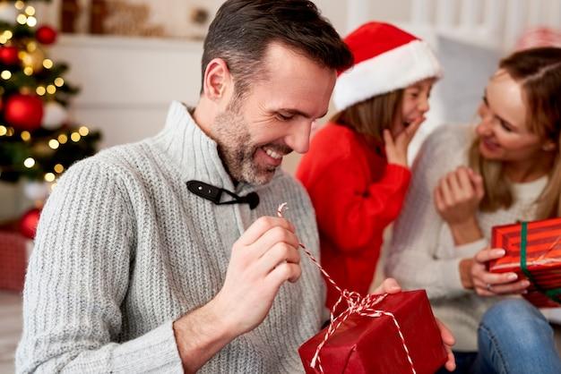 Szczęśliwy człowiek otwierając prezent na boże narodzenie
