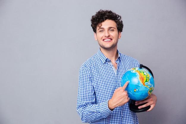 Szczęśliwy człowiek palcem wskazującym na całym świecie