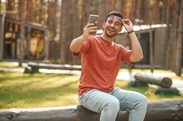 Szczęśliwy człowiek patrzący na smartfona w wyciągniętej dłoni