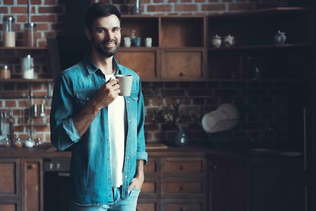 Szczęśliwy człowiek pijąc kawę podczas przerwy w kuchni.